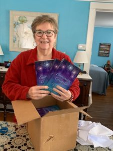 Marion Andrews holding copies of her book, Gloriously Grateful